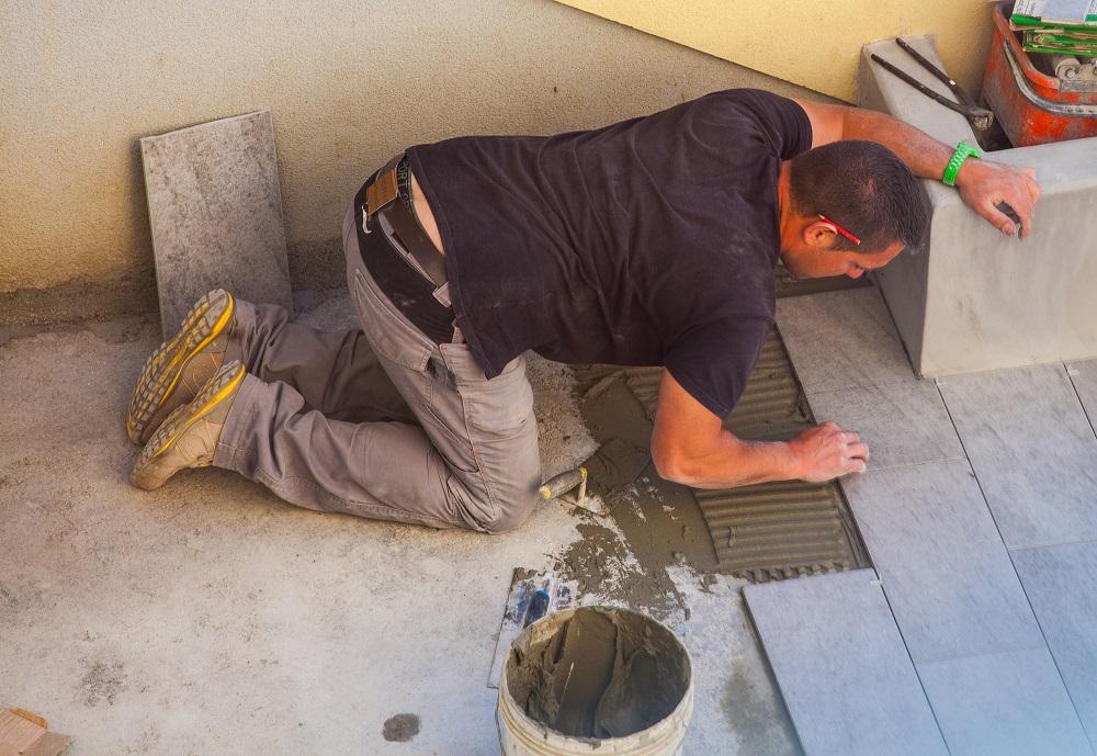Robotnik układa płytki podłogowe